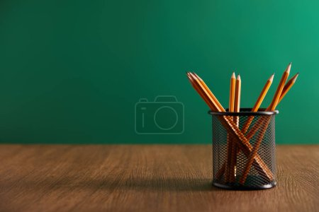 pencils on wooden table with green chalkboard on background
