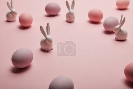 toy bunnies and painted easter eggs on pink background