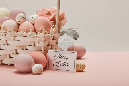 easter chicken and quail eggs in straw basket with flower and card with happy easter lettering