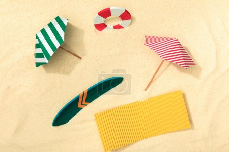top view of paper beach with lifebuoy, umbrellas, surfboard and towel on textured sand