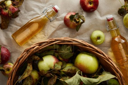 top view of basket with apples near glass bottles with cider