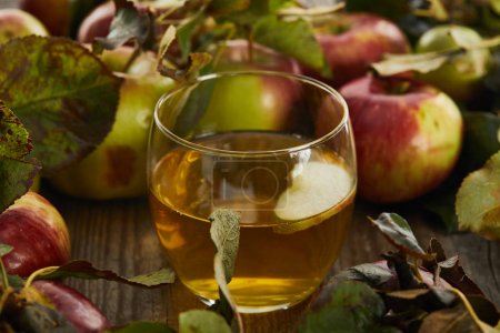 glass of fresh cider near apples on wooden surface