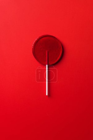 top view of one lollipop on red surface