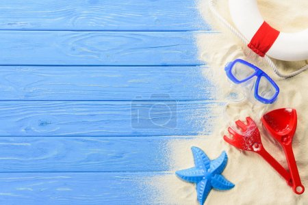 Diving mask and beach toys on blue wooden background
