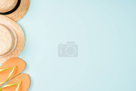 top view of straw hats and flip flops on blue background