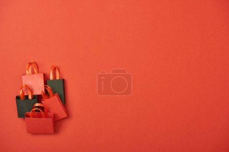 top view of shopping bags on red background with copy space