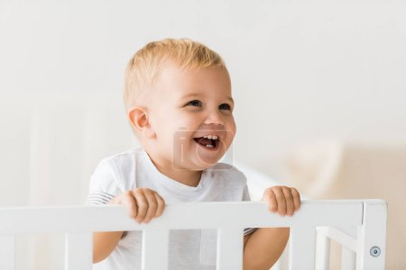 cheerful toddler standing in baby crib on white background