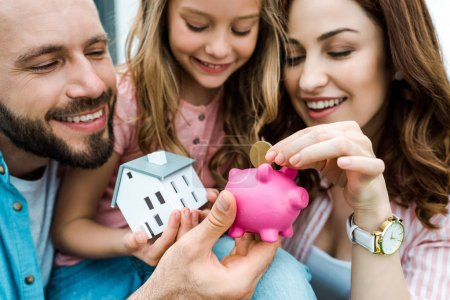 selective focus of happy woman putting golden coin in piggy bank near husband and daughter
