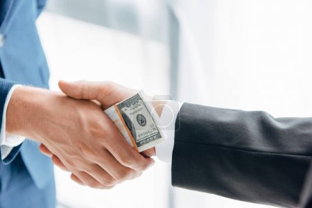 cropped view of businessman giving bribe to business partner while shaking hands in office