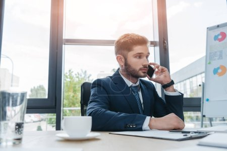 young businessman talking on smartphone while sitting at desk in meeting room