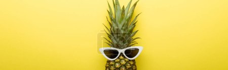 top view of ripe pineapple in sunglasses on yellow background, panoramic shot