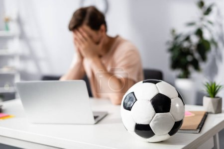 Selective focus of football on table and sad man covering face with hands near laptop at home, earning online concept