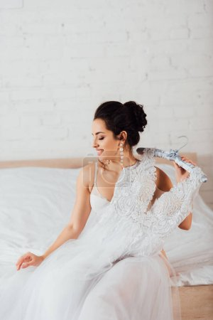 Bride in bra and pearl earrings holding hanger with white wedding dress on bed at home