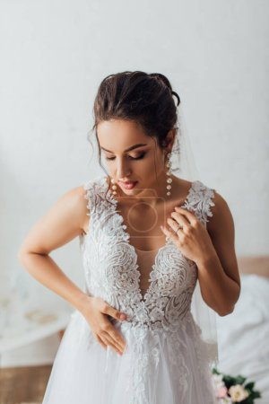 Selective focus of brunette bride touching lace wedding dress at home
