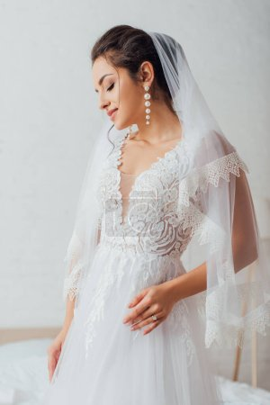 Young bride wearing in pearl earrings, veil and wedding dress at home