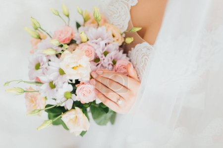 Cropped view of bride in wedding dress and veil holding floral bouquet