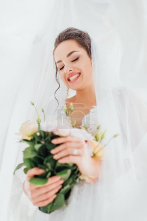 Selective focus of young bride in veil and dress holding floral bouquet