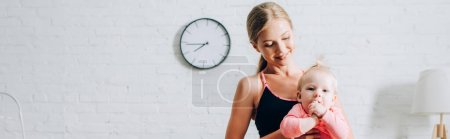 Panoramic orientation of mother in sports top holding infant daughter at home
