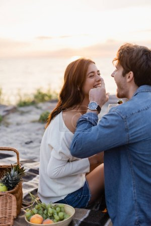 Selective focus of man with bottle of wine laughing while touching nose of girlfriend during picnic on beach