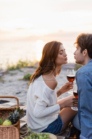 Selective focus of young couple kissing while holding glasses of wine during picnic on beach