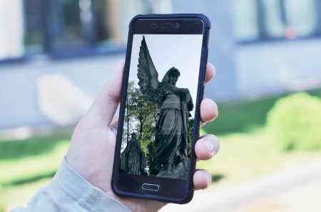 Man taking a photo of statue by smartphone. Looking at photography on display. Making content for social media