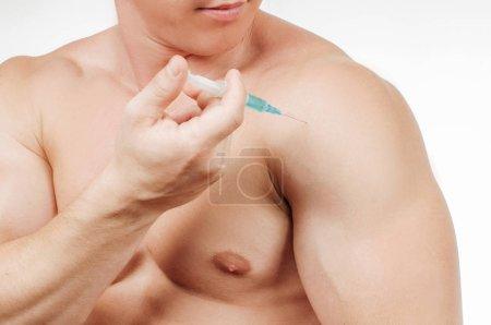 Bodybuilder taking steroids injection in shoulder. Man is taking steroids