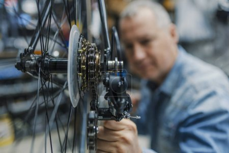 Service for bike with adept repairing bike. Bicycle mechanic in a workshop in the repair process. Stylish bicycle mechanic doing his professional work in workshop.
