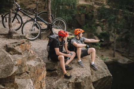 high angle view of young trial bikers relaxing on rocky cliff after ride and looking away