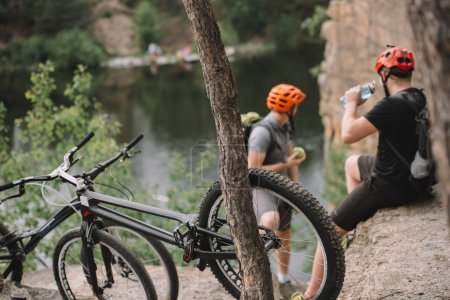 young trial bikers relaxing on rocky cliff after ride with bicycles on foreground