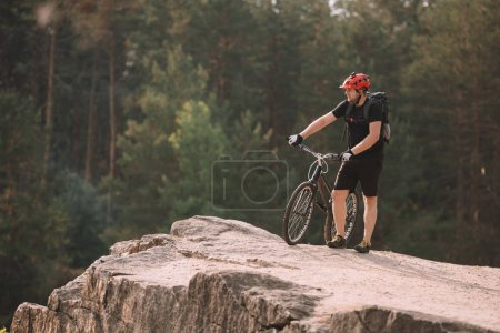 young trial biker standing on rocky cliff outdoors and looking away