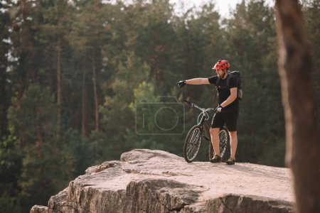 young trial biker standing on rocky cliff outdoors and pointing somewhere