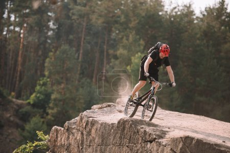 young trial biker riding on rocky clifff outdoors