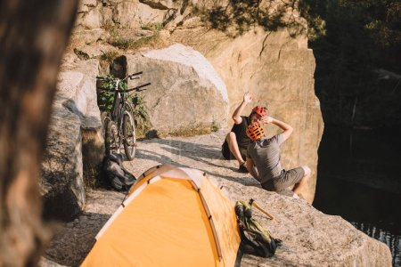 high angle view of active trial bikers sitting on rocky cliff with camping tent and giving high five